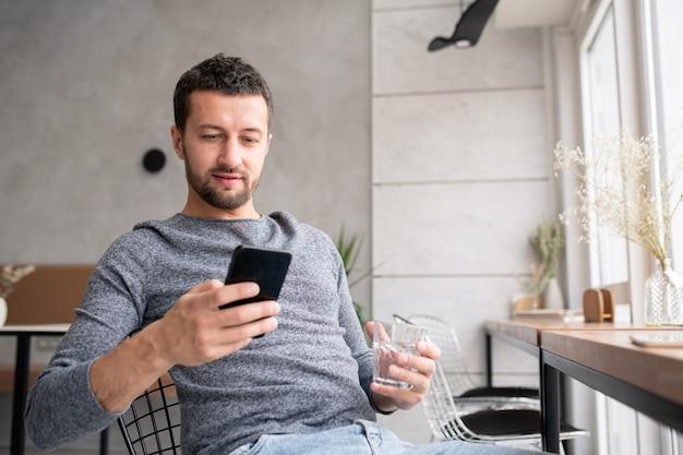 Jovem descansado relaxando em um café aconchegante, tomando um copo d'água e rolando ou enviando mensagens no smartphone