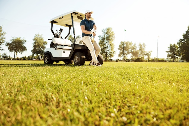 Jovem descansando enquanto inclinando-se em um carrinho de golfe