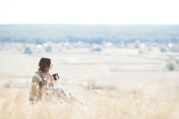 Jovem, descansando na natureza. fêmea no prado bebendo chá quente.