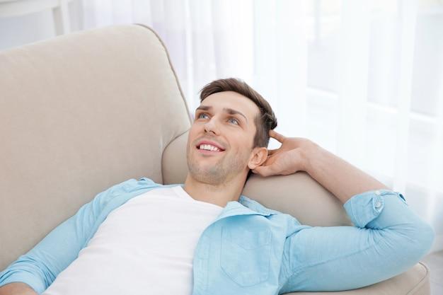 Jovem descansando no sofá com a mão atrás da cabeça em uma sala iluminada