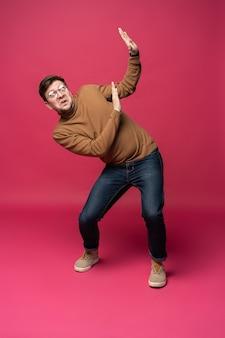 Jovem descolado de corpo inteiro com medo de pose isolado em fundo rosa da moda