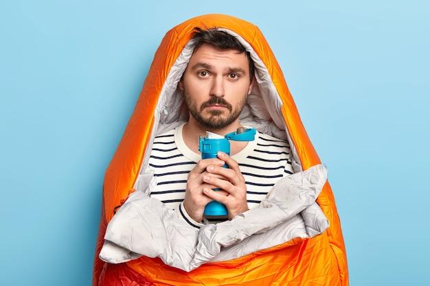 Jovem descontente com a barba por fazer, sente frio depois de passar a noite ao ar livre, bebe bebida quente da garrafa térmica, embrulhado em saco de dormir
