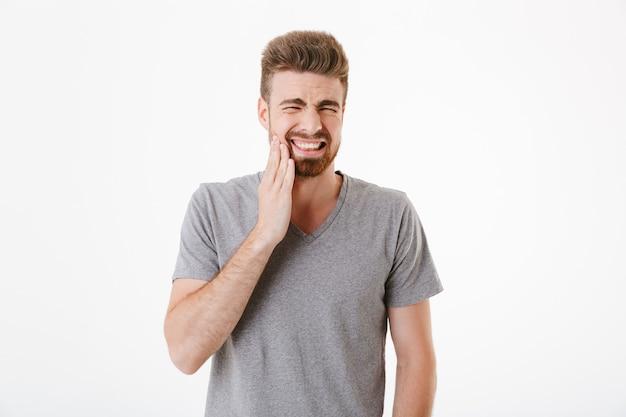 Jovem descontente com dor de dente em pé isolado Foto Premium