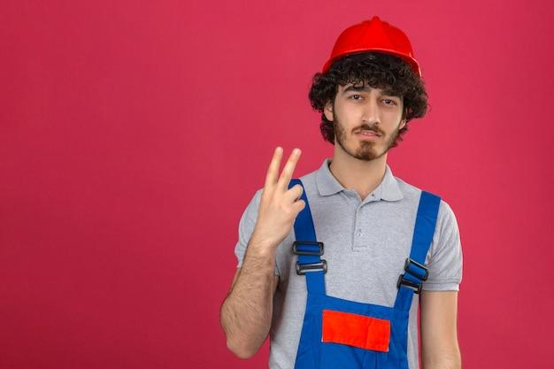 Jovem descontente empanado bonito construtor, usando uniforme de construção e capacete de segurança aparecendo e apontando para cima com os dedos número dois sobre fundo rosa isolado