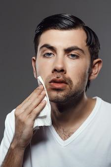 Jovem descontente tocar o rosto depois de barbear sobre parede cinza