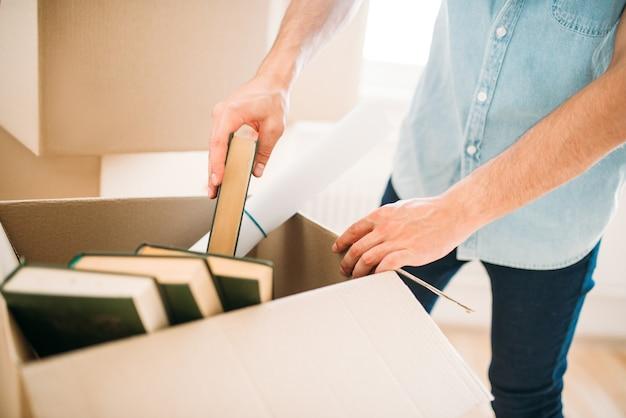 Jovem desempacotando caixas de papelão, inauguração de casa