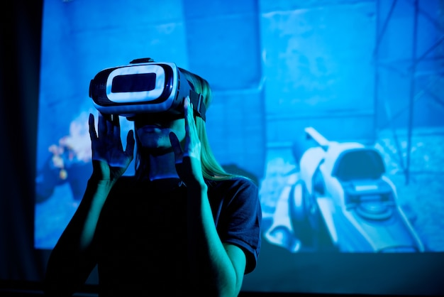 Jovem desenvolvedor de um novo videogame futurista com fone de ouvido vr em pé contra uma tela grande com máquinas virtuais durante a apresentação