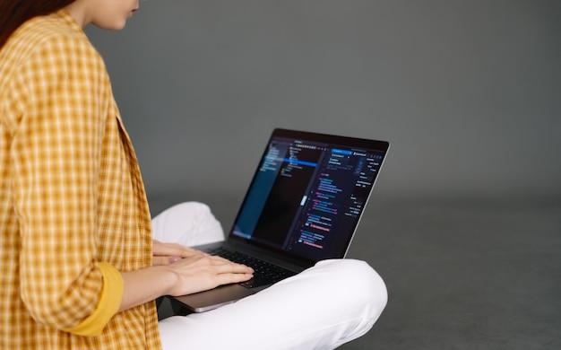 Jovem desenvolvedora de dispositivos móveis escreve código de programa em um trabalho de programador de computador