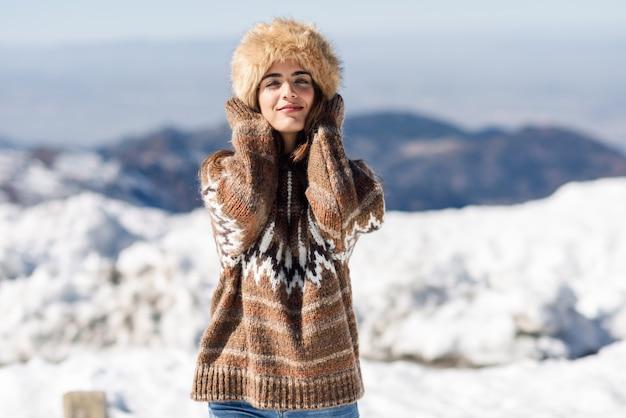 Jovem, desfrutando das montanhas nevadas no inverno