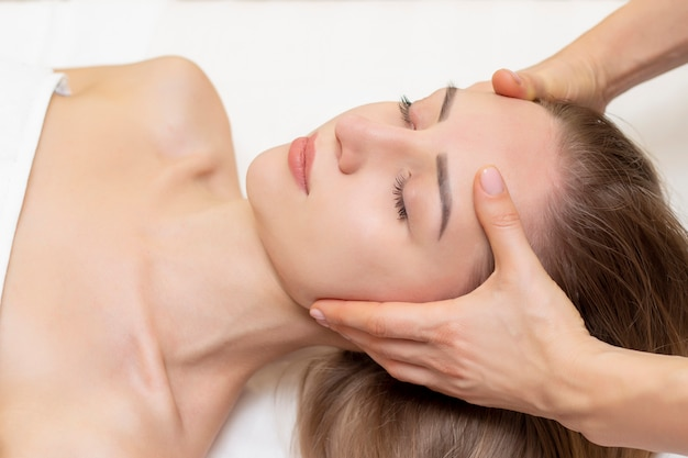 Jovem, desfrutando de massagem no salão spa. massagem de rosto. closeup de jovem recebendo tratamento de massagem spa no salão de beleza spa. cuidados com a pele e o corpo. tratamento de beleza facial.