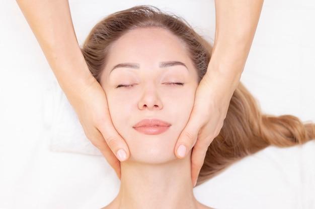 Jovem, desfrutando de massagem no salão spa. massagem facial