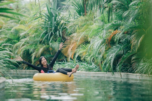 Jovem, desfrutando de tubulação na piscina do rio lento