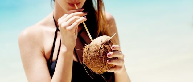 Jovem, desfrutando de um cocktail numa praia linda com água turquesa.