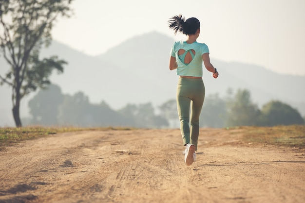Jovem, desfrutando de um estilo de vida saudável, enquanto corre ao longo de uma estrada secundária, exercício e fitness e treino ao ar livre. jovem correndo em uma estrada rural durante o pôr do sol.