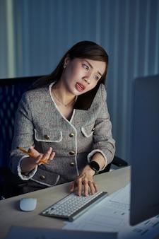 Jovem designer asiática de interface do usuário trabalhando em um escritório escuro tarde da noite, atendendo uma ligação de um cliente e fazendo alterações na maquete da interface