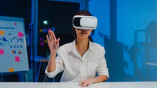 Jovem designer asiática usando óculos vr (realidade virtual), testando o aplicativo móvel do software de desenvolvimento na noite do escritório em casa criativo moderno. distanciamento social, quarentena para prevenção do vírus corona.