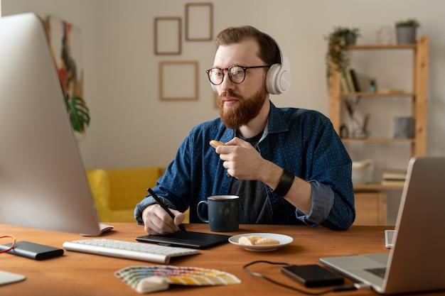 Jovem designer barbudo ocupado usando fones de ouvido sem fio, sentado à mesa no escritório em casa e comendo biscoitos enquanto trabalha com o computador e o digitalizador