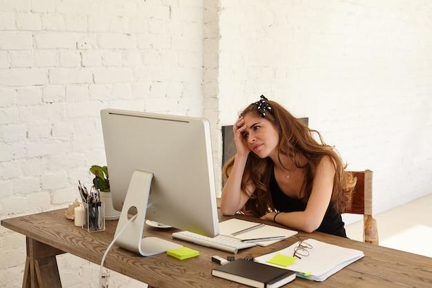 Jovem designer caucasiana se sente em pânico com o prazo final para seu trabalho, sentada no local de trabalho com papéis, um bloco de notas e olha para o monitor do computador contra a parede de tijolos brancos, parecendo intrigada