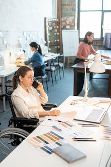 Jovem designer criativo em uma cadeira de rodas, sentado à mesa em frente ao laptop, olhando ideias online e ligando para um dos clientes