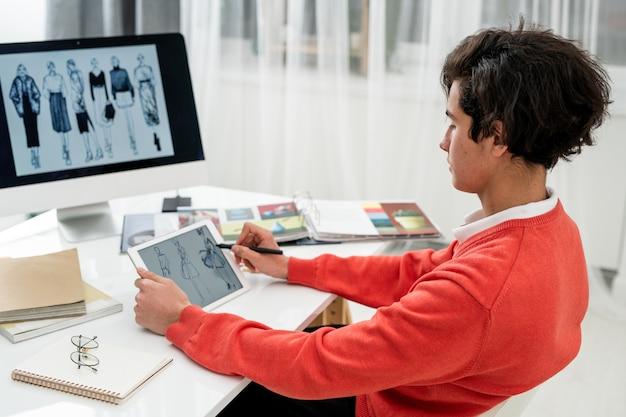 Jovem designer de moda procurando novos modelos no touchpad enquanto está sentado na mesa em frente à tela do computador