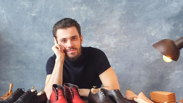 Jovem designer de sapatos, olhando para a câmera mostra seu trabalho