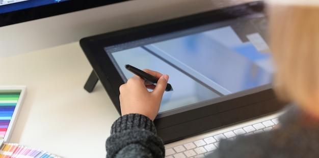 Jovem designer desenhando esboços em tablet gráfico