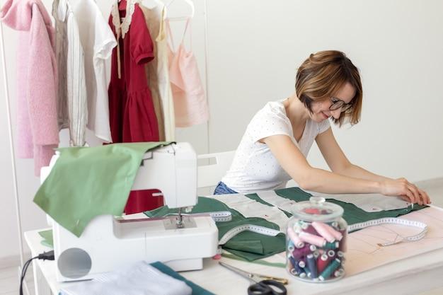 Jovem designer faz marcas para um novo produto de costura sentado à mesa ao lado da máquina de costura. conceito de design e negócios criativos.