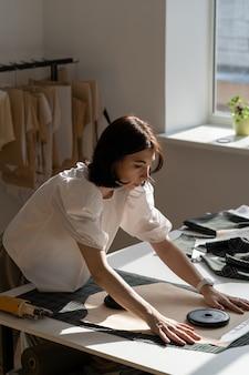 Jovem designer feminina colocou padrão em tecido para cortar modelo de trabalho de costureira com têxteis no ateliê