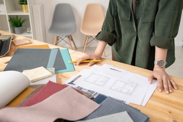 Jovem designer feminina e criativa em casualwear, em pé ao lado da mesa e trabalhando com o esboço da casa no papel em estúdio