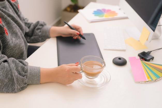 Jovem designer feminino asiático usando mesa digitalizadora enquanto trabalhava com o computador no estúdio ou escritório.