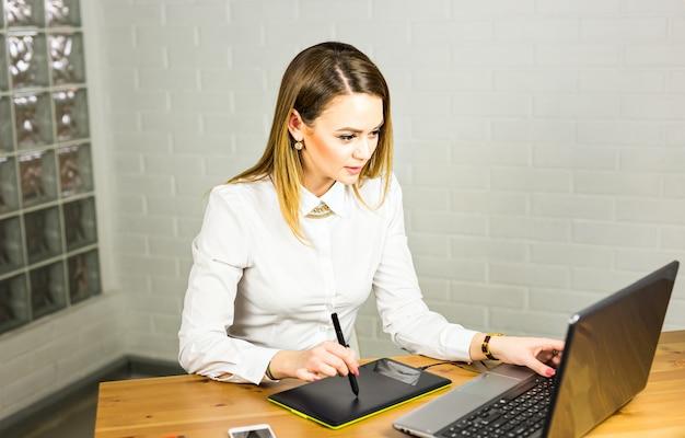 Jovem designer feminino usando a mesa digitalizadora enquanto trabalhava com o computador