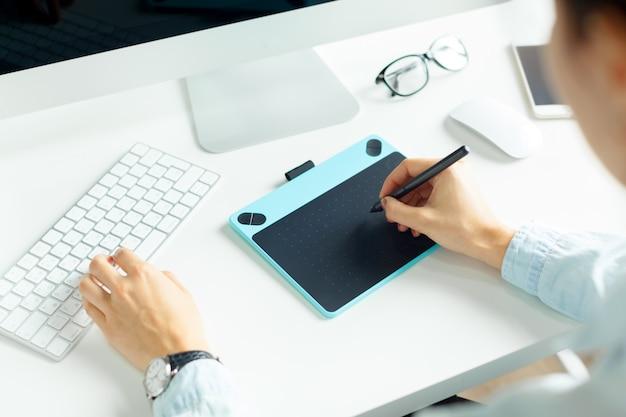 Jovem designer feminino usando a mesa digitalizadora