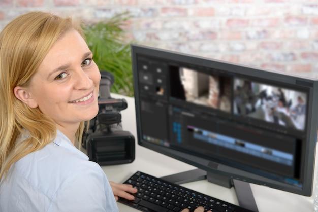 Jovem designer feminino usando computador para edição de vídeo
