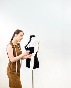 Jovem designer feminino vestido de costura na loja
