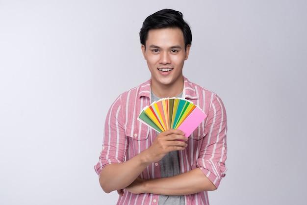 Jovem designer gráfico asiático segurando paleta de cores