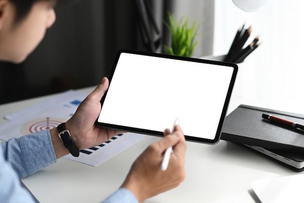 Jovem designer gráfico com caneta stylus apontando na mesa gráfica com tela em branco.