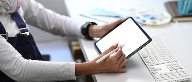 Jovem designer gráfico esboçando seu projeto com tablet digital em seu local de trabalho criativo.