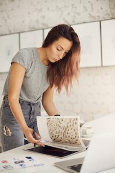 Jovem designer gráfico folheando uma revista em busca de inspiração para um cliente que usa um laptop.