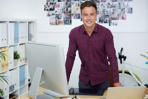 Jovem designer gráfico ou fotógrafo positivo em frente à sua mesa de escritório com um computador e uma mesa digitalizadora