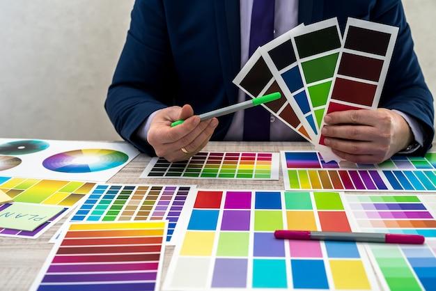 Jovem designer gráfico ou interior de terno, escolhendo a cor de amostra de amostra ou guia de paleta de catálogo no local de trabalho. designer gráfico com amostras de paleta de cores de tinta na mesa, close-up