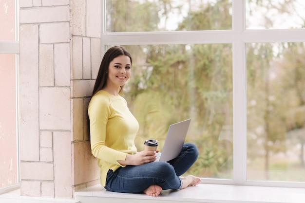 Jovem designer gráfico trabalhando em casa. mulher sentada no peitoril da janela com laptop e bebe café.