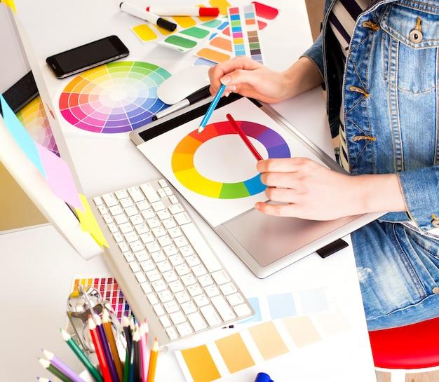 Jovem designer gráfico usando tablet gráfico
