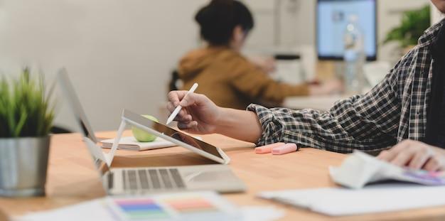 Jovem designer masculino, planejando seu projeto com uma colega de trabalho em segundo plano