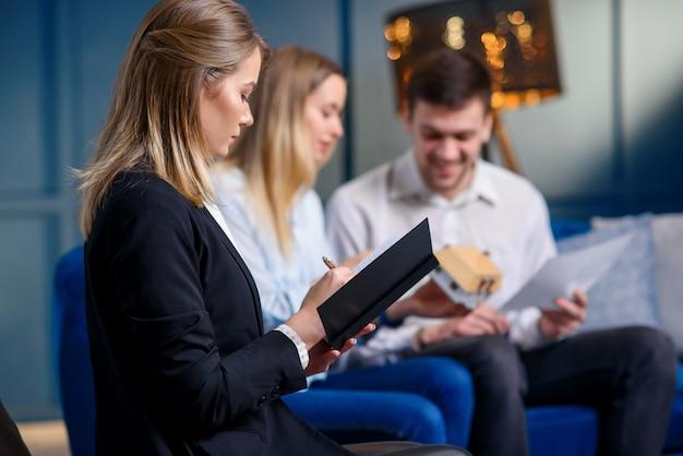 Jovem designer, observando as idéias de alguns clientes sobre o design da futura casa no notebook.