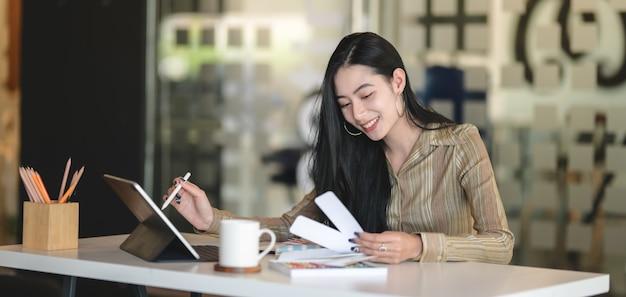 Jovem designer profissional feminino, trabalhando em seu projeto enquanto estiver usando tablet digital no escritório moderno