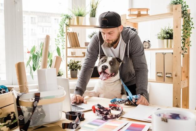 Jovem designer sério em roupas casuais, curvado sobre a mesa em frente ao laptop enquanto navega na internet em busca de novas ideias com seu animal de estimação
