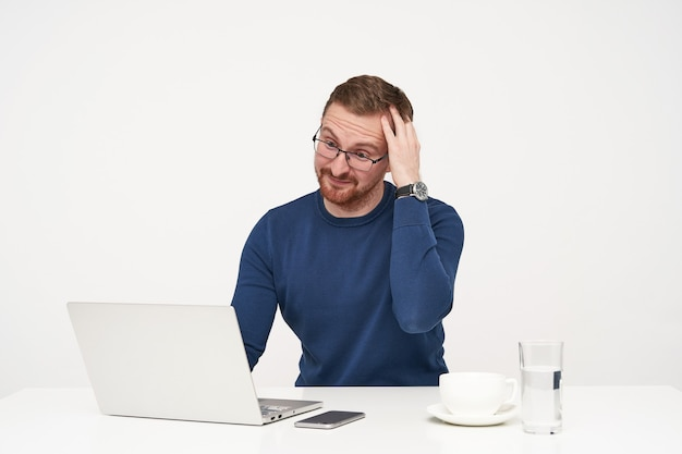 Jovem, desnorteado, bonito, barbudo, de óculos, mantendo a mão erguida sobre a cabeça e a testa franzida, enquanto olha confuso para seu laptop, isolado sobre um fundo branco