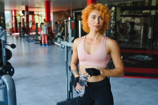 Jovem desportista a relaxar após treinar e a beber água no ginásio