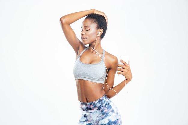 Jovem desportista afro-americana fofa espantada a ouvir música no telemóvel