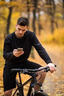 Jovem desportista andando de bicicleta, segurando o telefone, parque ensolarado de outono